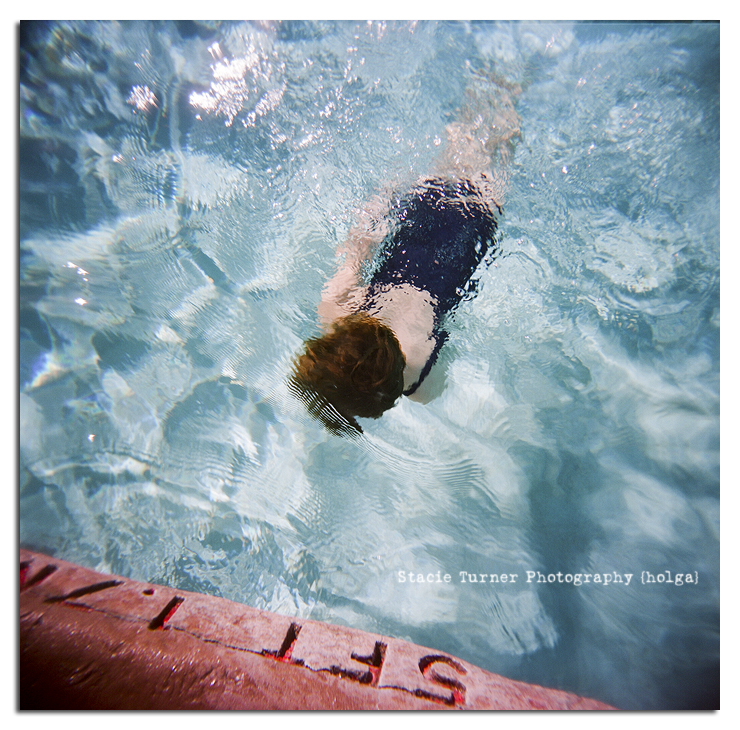 holga image of a child swimming in a pool