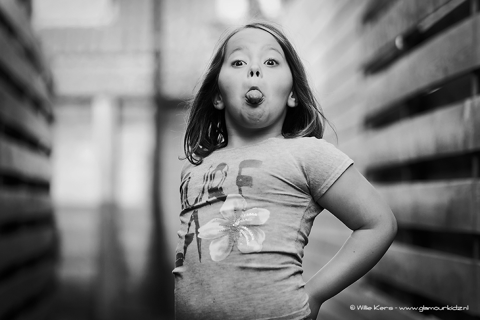black and white image of a girl sticking her tongue out at the camera by Willie Kers glamourkidz photograpy portrait