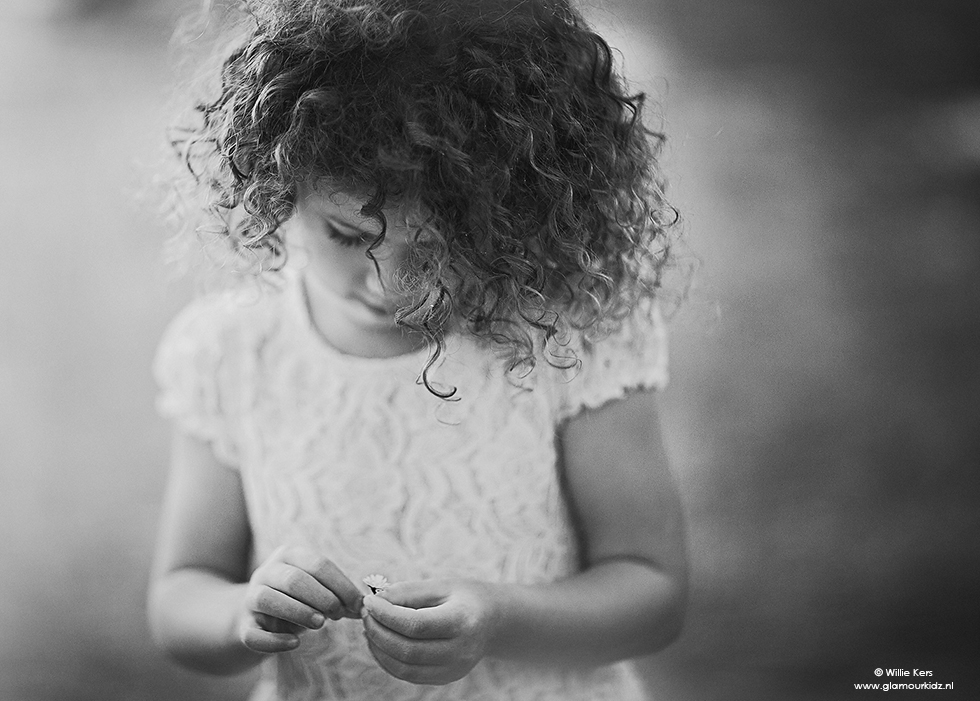 Black and white image of a girl with a little daisy