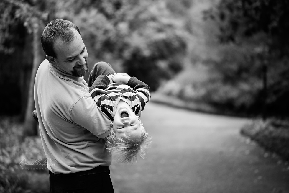 Black and white image of little boy hanging upside-down in daddy's arms laughing | Danielle Parker Photography