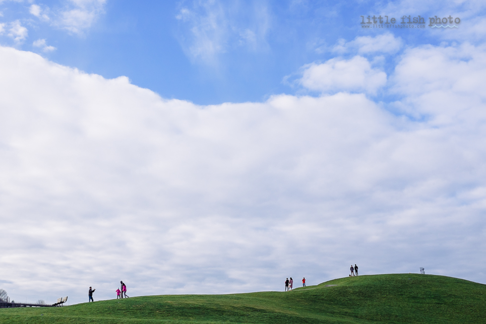 people walking along the horizon of a big hill under a blue cloudy sky