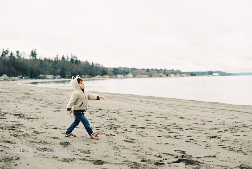 boy in bear coat marching on beach