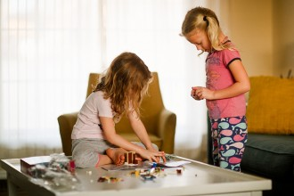 two girls building legos by April Nienhuis