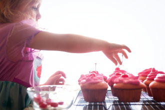 toddler girl decorating pink cupcakes with cherry