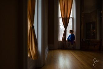 Little-Girl-Looking-Out-Window-in-Fancy-Room-with-Yellow-and-Blue-Color-Contrast-