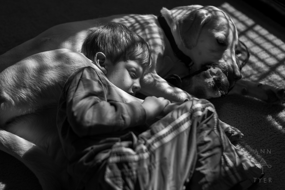 A boy laying with his dog