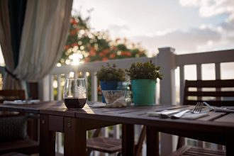 cheers-glass-of-red-wine-sitting-outside-during-golden-hour-hawaii-photographer-allison-gipson