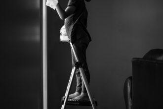 little-girl-washing-window-dramatic-light-indoor-photography-natural-light-Sarah-Hodges