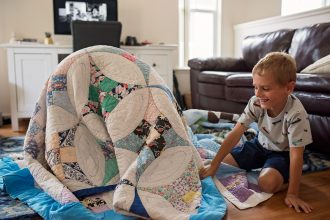 boy-dog-playing-with-old-antique-quilts-lifestyle-documentary-allison-gipson-hawaii-photographer