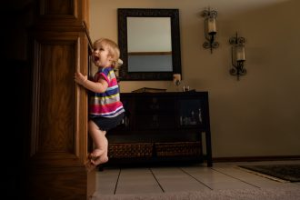 Climbing Claire toddler girl climbing pillar in home edmond oklahoma city lifestyle photography