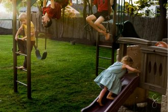 Four-Children-in-the-Frame-Playing-on-Playset-in-Beautiful-Light-and-Colorful-Setting-by-Sarah-Wilkerson-
