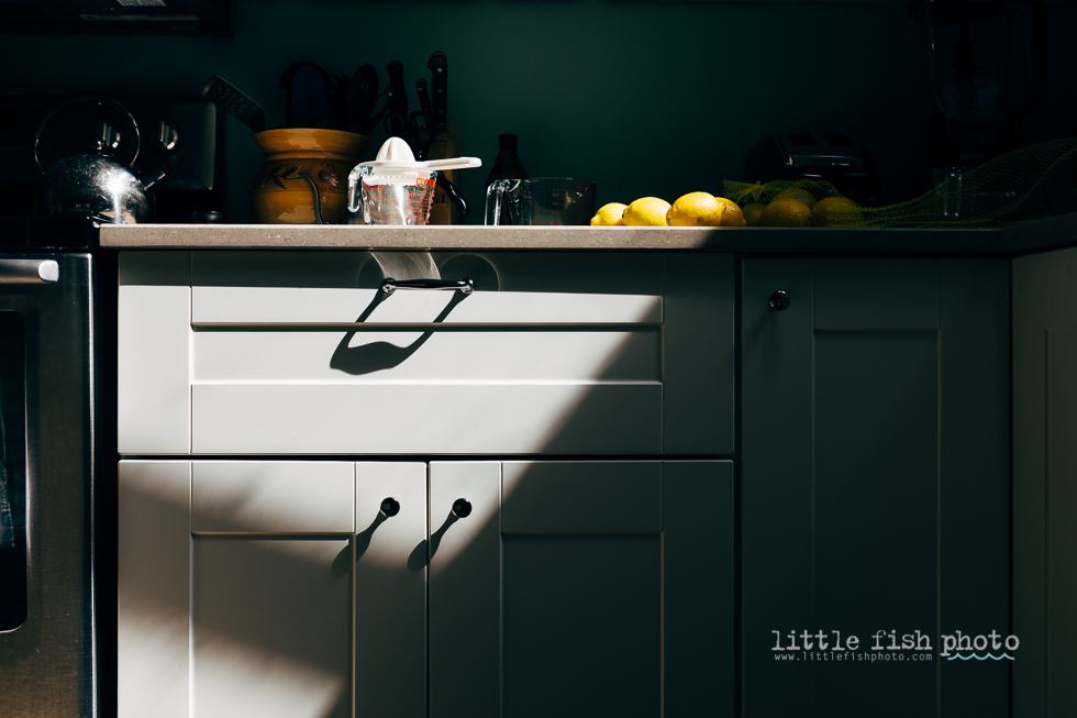Lemons and Measuring cup on sunlit kitchen counter