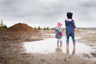 sisters stand in a mud puddle in Alberta, Canada
