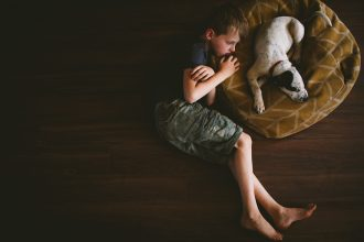 picture of boy snuggled up next to a sleeping puppy by April Nienhuis