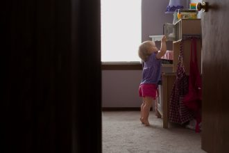 tippy toes toddler girl reaching for food in ikea play kitchen edmond oklahoma city photographer