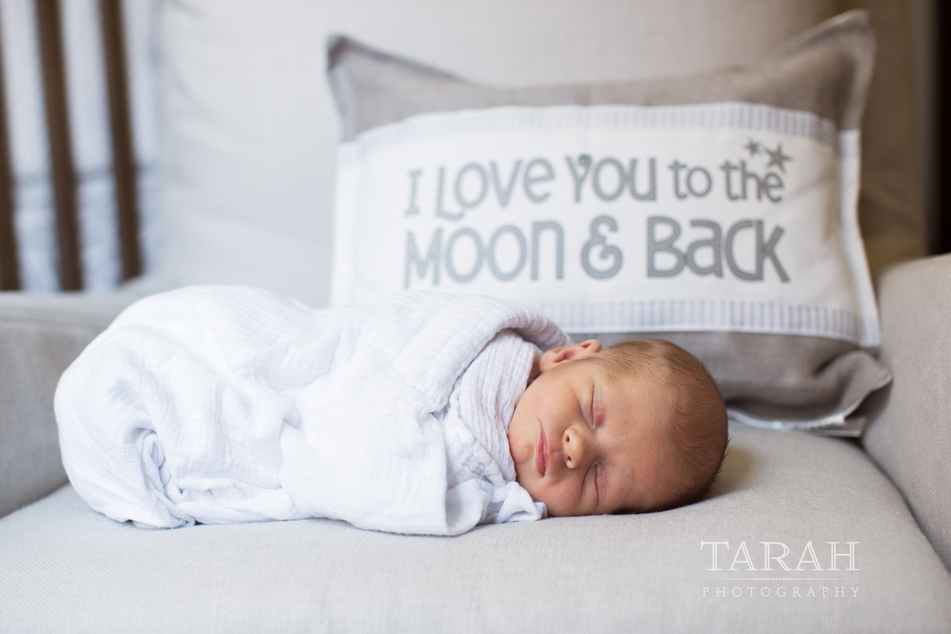newborn boy swaddled sleeping in front of pillow that reads love you to the moon and back