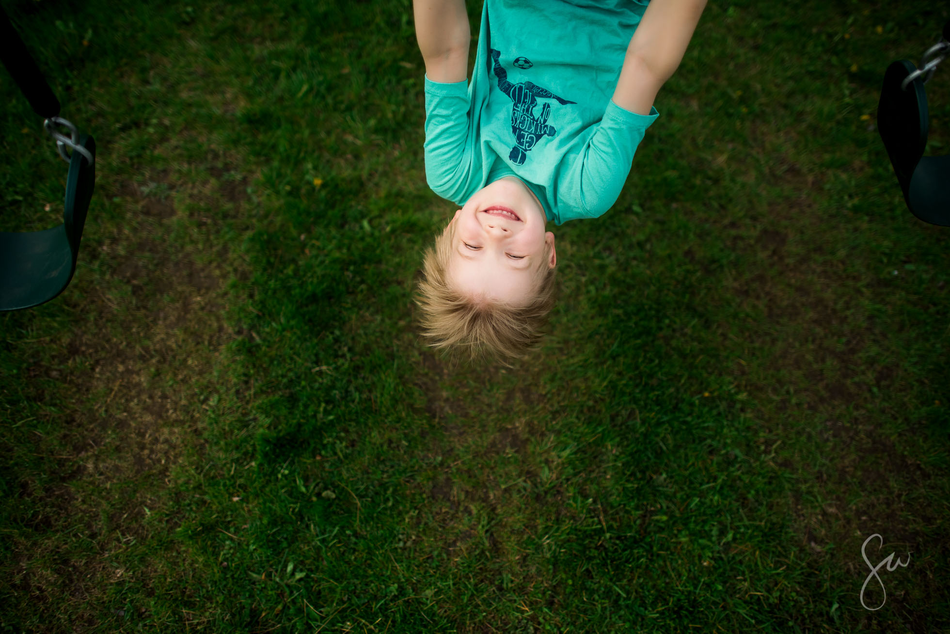 Joyful-Face-of-Child-Hanging-Upside-Down-on-Swings-by-Sarah-Wilkerson-