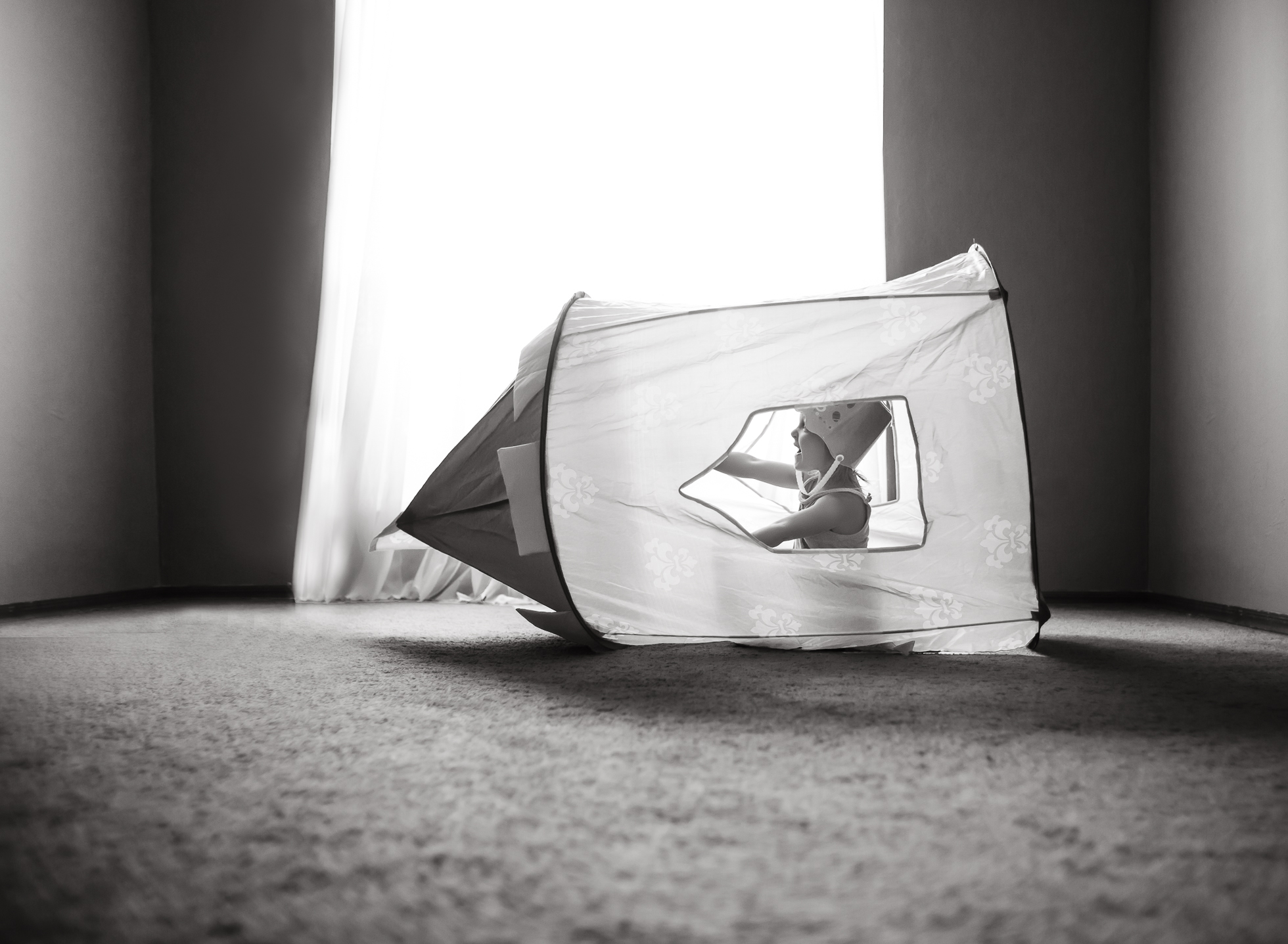 Blast off young girl playing in castle tent rocket ship imagination black and white edmond oklahoma