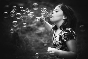Fujifilm xpro2 and lensbaby black and white portrait of a girl blowing bubbles by willie kers