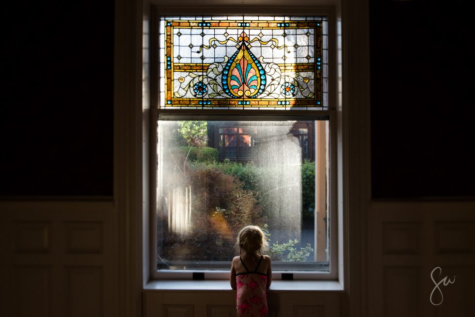 Tilt-Shift-Portrait-of-Little-Girl-Looking-Out-Stained-Glass-Window-on-Summer-Evening-by-Sarah-Wilkerson-