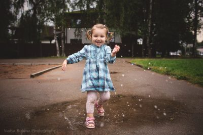 A girl making splashes in puddle