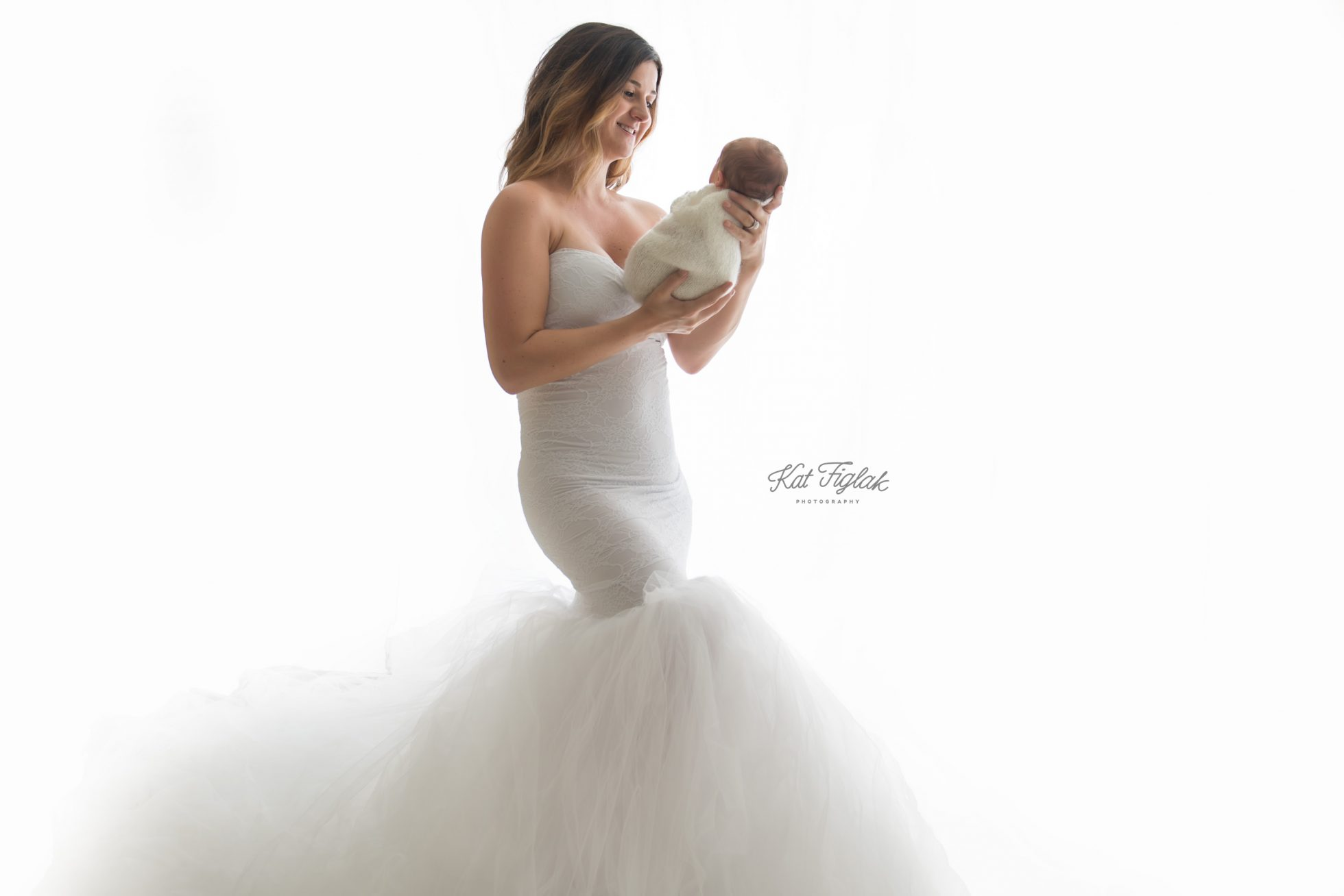 A new mother in a white gown holding her baby girl