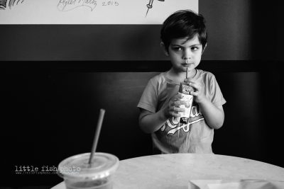 boy makes face while drinking milk at coffee shop