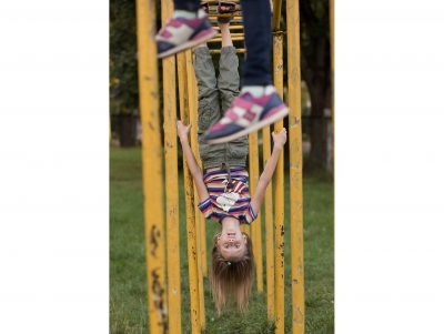 A tween girl hanging upside down