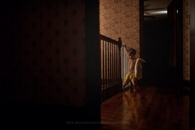 Little boy in hall with yellow shorts holding lovie