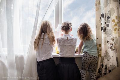 Three sisters dressed up and looking through a window in their first day of school