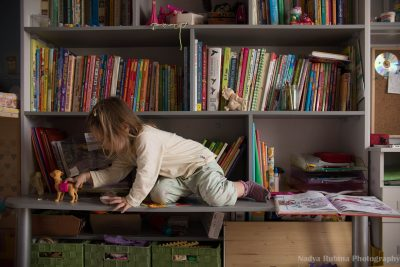 A toddler girl playing on a book shelf among the books