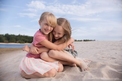 Tween aged sisters hugging and laughing on the beach