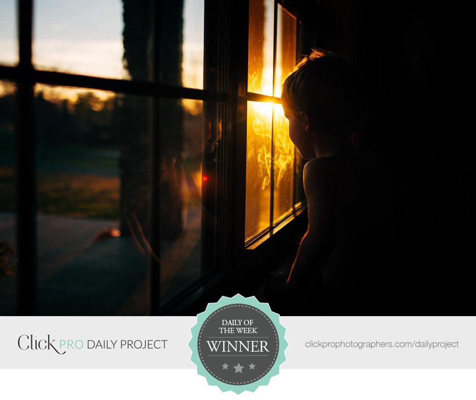 boy-looking-through-window-sunset-by-amber-walder