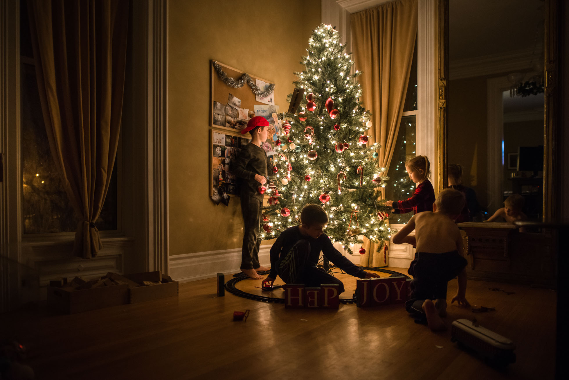 documentary-holiday-lifestyle-photo-of-four-children-decorating-a-classic-american-christmas-tree-in-low-light-by-sarah-wilkerson-3816