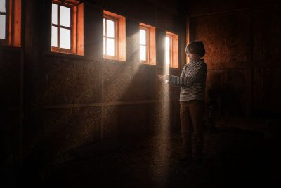 boy standing in barn holding dust that glitters in the light