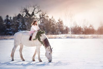 girl wearing a princess crown riding a white horse