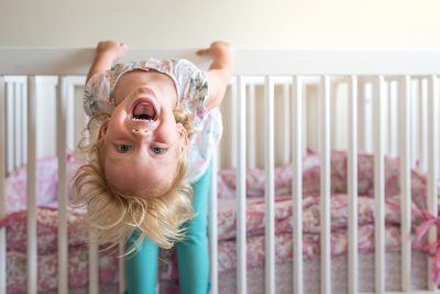 little girl hanging upside down in her crib
