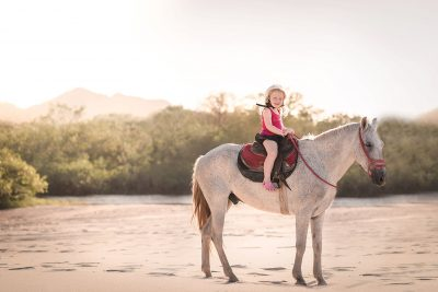 little girl riding a horse in guanacaste