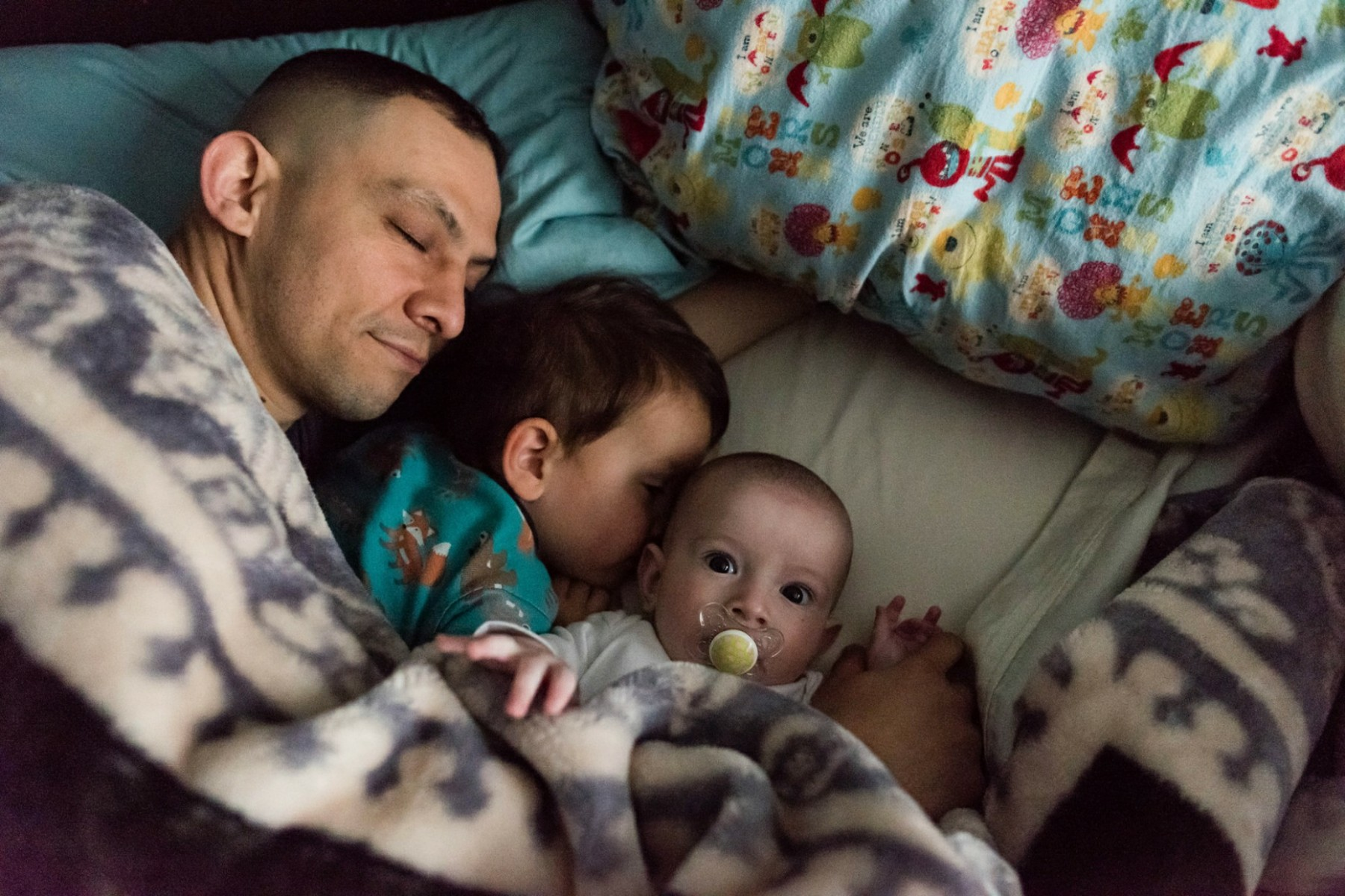 Father snuggling in bed with toddler and baby sons
