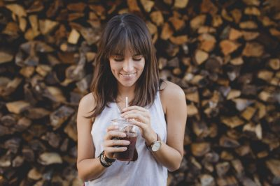 Young woman drinking iced coffee outside.