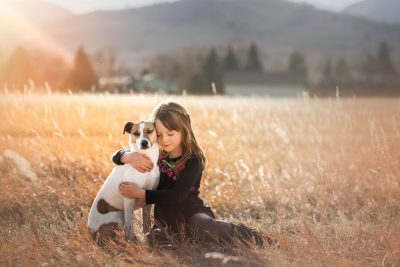 girl hugging her dog in a field at sunset