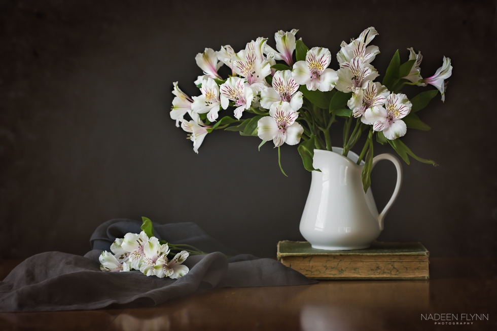 bouquet of alstroemeria in white pitcher on old book