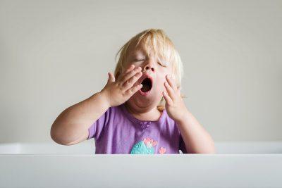 little girl yawning in crib