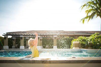 little girl splashing in the pool