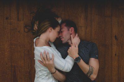 Couple cuddling on hard wood floor by Tami Keehn