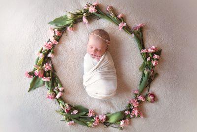 newborn baby sleeping inside flower wreath