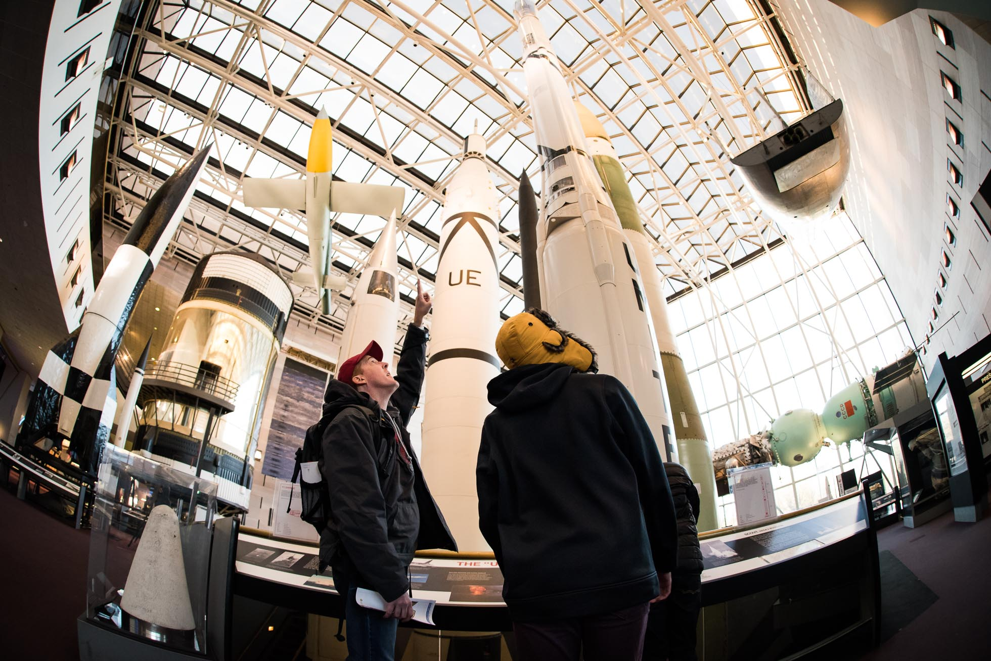 Fish eye image of a dad with his son at the National Air and Space Museum - pointing up at the rockets