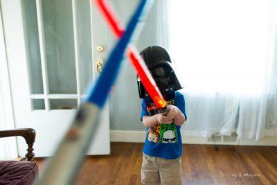 boy-in-darth-vader-mask-playing-light-saber