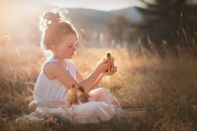 little girl holding ducklings