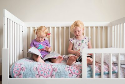 two little girls reading in bed